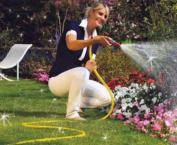 Женщина из шланга поливает цветы