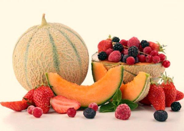 Дыня и разнообразные ягоды на столе