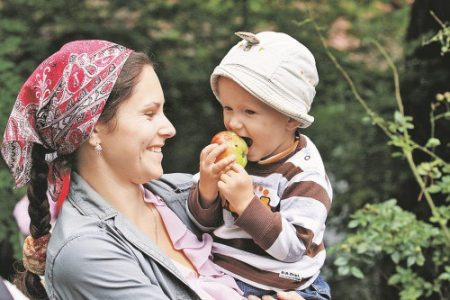 Ребенок ест яблоко, не пораженное болезнями и вредителями