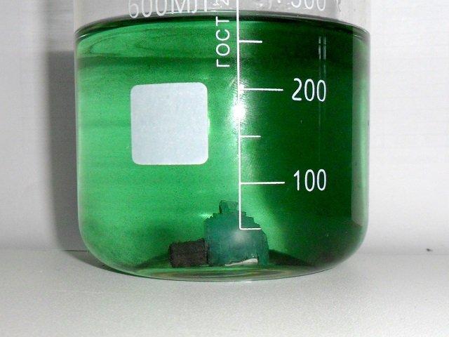 Кристалл железного купороса в градуированном сосуде с водой
