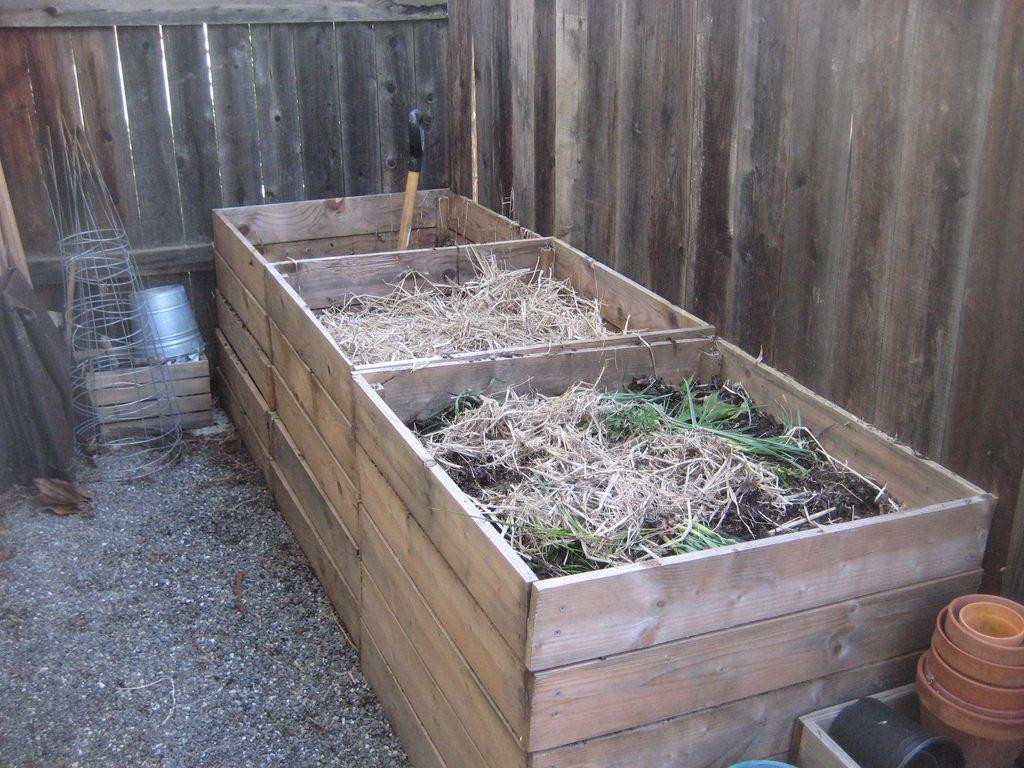 Компост из скошенной травы в деревянных ящиках